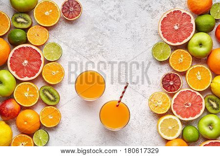 Fresh juices or smoothies with citrus fruit, apple, kiwi on light background. Top view, selective focus. Detox, dieting, clean eating, vegetarian, vegan, fitnes healthy lifestyle concept