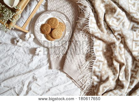 Breakfast in bed concept - oatmeal cookies. Warm, soft, light colors, warm plaid, cotton flowers, notepad in the frame with copy spase. Flat lay style.