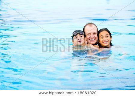 Man with two children having fun in the tropical swimming pool