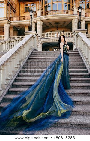 Young woman in a luxurious blue dress with a long train on the architecture background