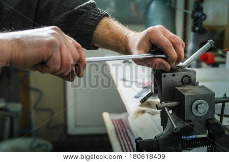 Mechanics repairing a diesel injector. Man's hand holding a wrench and untwists detail pinched in a vise.
