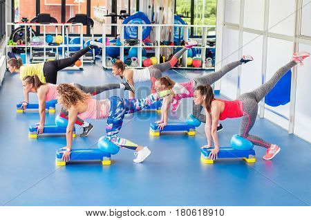Group Of Beautiful Young Women Working Out On Blue Stepper And Smiling.