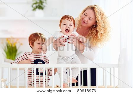 happy mother enjoying maternity playing with kids at home