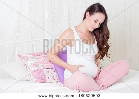 Happy Pregnant Woman Sitting On The Bed. A Young Pregnant Woman Is Sitting In The Bedroom. Pregnant