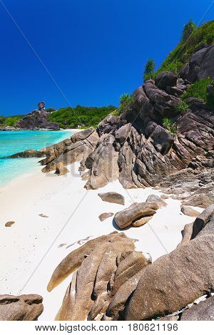 The tropical island with the beach to the sea white sand with boulders and large stones. It is covered with green trees and vegetation.