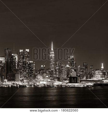 Midtown skyline over Hudson River in New York City with skyscrapers at night