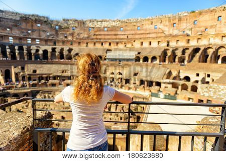 ROME, ITALY - MAY 10, 2014: The golden-haired female tourist looks at the Colosseum in Rome, Italy. The Colosseum is an important monument of antiquity and is one of the main tourist attractions of Rome.