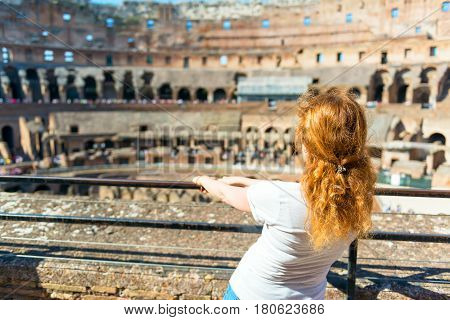 ROME, ITALY - MAY 10, 2014: Female redhead tourist inside the Colosseum. The Colosseum is an important monument of antiquity and is one of the main tourist attractions of Rome.