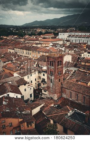 Lucca rooftop view with red roofs of historic buildings and mountain range in Italy.