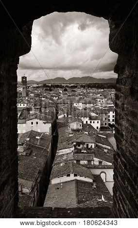 Lucca town skyline rooftop view through window in Italy.