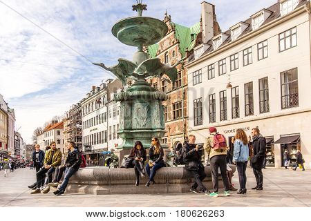 The Stork Fountain with young people sitting on the edge. Amagertorv in central Copenhagen Denmark - Mars 23 2017