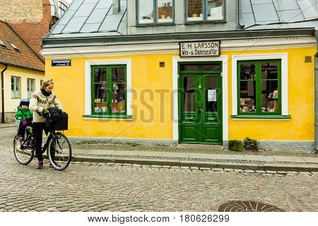 Woman with child on a bike stopping in front of an old retro wine-store in the town of Lund Sweden - Mars 25 2017
