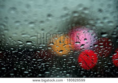 View of the night city through the window on a rainy night, raindrops fall on the windshield of the car. Concept life of a modern city. Abstract background for banner design