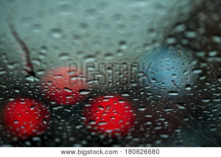 Night city in rain, urban life and street lights, dense traffic. Water drops on the glass. Abstract background. Concept life of a modern city at night.