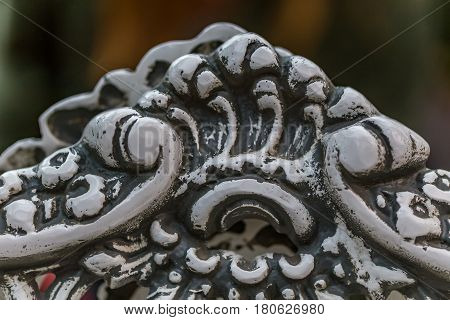 Pattern detail on a wrought iron bench in a park.