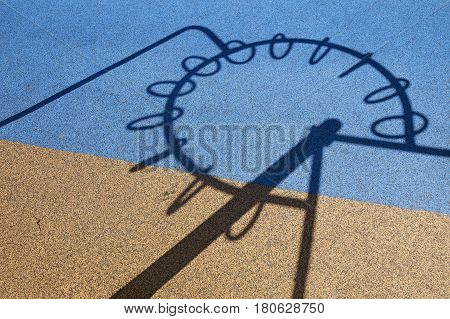 shadow from the playground on the rubber surface. The shadow from the playground resembles the symbol of the European Union on a two-color covering, which resembles the flag of Ukraine
