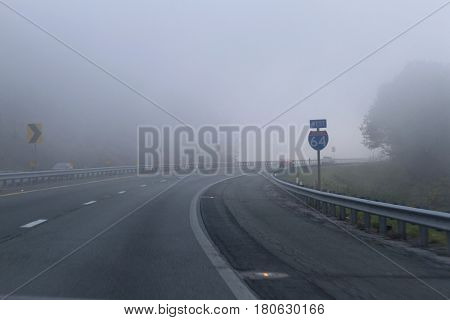Cars drive through the Blue Ridge Mountains into early morning fog on Interstate 64