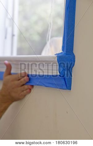 close up; young; male; hand; applying; blue; painter; tape; around; window; frame; interior; house; painting; occupation; working worker trade room; protect; before; painting; adjoining; wall; preparation; renovation; work; tool; covering; woodwork; prote