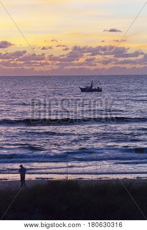 Silhouette of a fisherman on the beach and a fishing trawler on the water backlit by a multicolored sunset in Indian Rocks Florida both ready to head home after a long day of fishing the Gulf of Mexico
