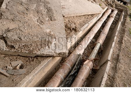 Old rusty water pipes in concrete trench. Underground utility and services pipe lay at the construction site. Repairing of water delivery system, vintage color.