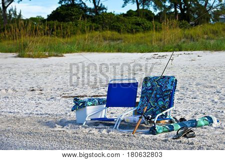 Two Beach Chairs with a Cooler Fsihing Pole Towels and an Umbrella on the Beach