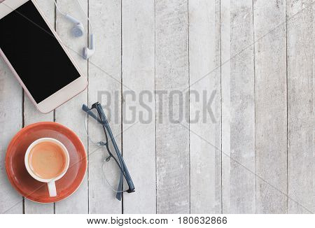 Coffee cup and smart phone with glasses on white wood background. Top view with copy space (selective focus). Office desk table concept.
