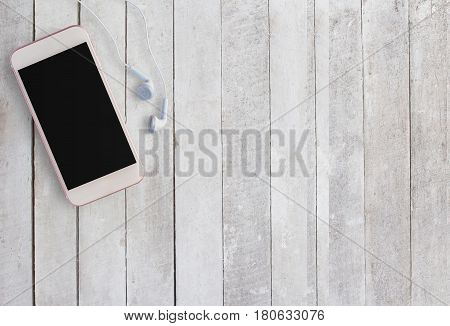 Smart phone and earphone on white wood background. Top view with copy space (selective focus). Office desk table concept.