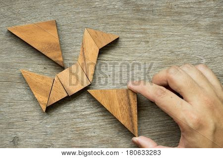 Man hold triangle to fulfill tangram puzzle in bird shape (Concept for freedom free life or explore new world)