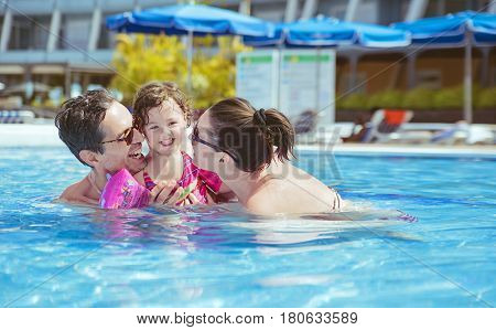 Vacation concept - happy family in a swimming pool