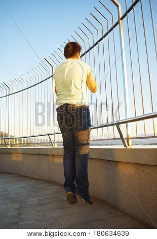 Happy Teen Boy Relaxing On Skyscraper Against Blue Sky