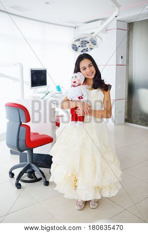 Little girl with a doctor-doll on the background of a dental clinic. Pediatrics.