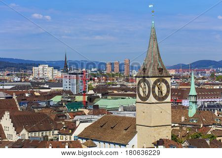 View of the city of Zurich from the tower of the Grossmunster cathedral with the clock tower of the Saint Peter Church in the foreground.
