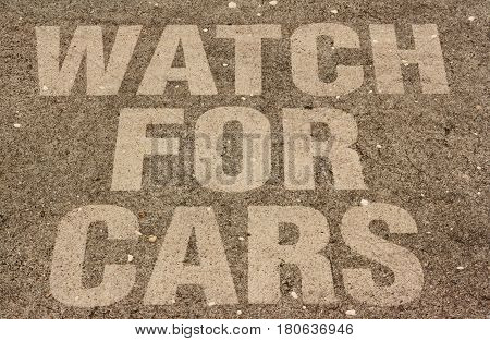 The words WATCH FOR CARS impedded into a course concrete walk