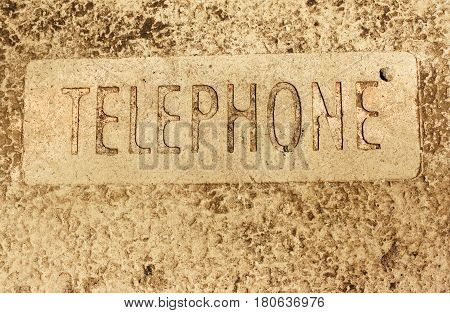 The word TELEPHONE embedded into a course concrete