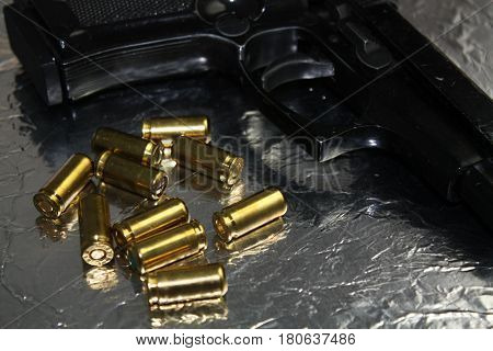 Pistol gun detail with brass golden munition on shiny silver desk