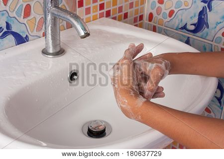 cloes up of hand girl washing hand with soap in toilet
