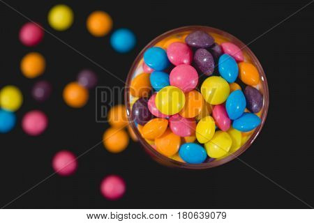 smarties in jar spilling our on black background