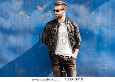 Portrait of a handsome man dressed in white t-shirt, jacket and jeans on the blue rusty wall background