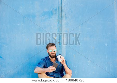 Man dressed casual in blue shirt sitting with phone and coffee to go on the blue wall background. Wide shot with copy space