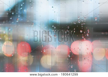 Photograph and digital manipulation of a traffic scene through a wet glass and with bokeh effect