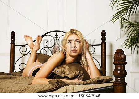 young pretty blond girl laying in cozy bed happy smiling, lifestyle people concept close up