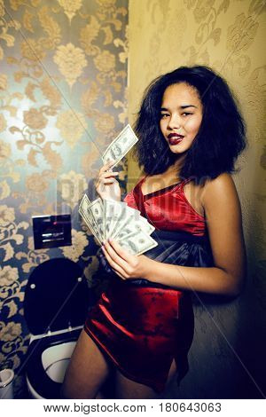 pretty young african american woman in luxury restroom with money
