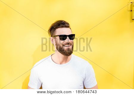 Colorful portrait of a handsome man dressed in white t-shirt on the yellow background