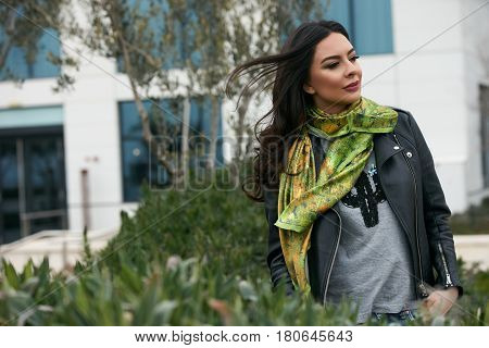 Portrait of Beautiful brunette young oriental beauty female  with black long hair Dressed in Leather jacket and denim pants with Oriental green scarf and oriental jewelry.