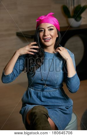 Portrait of Beautiful brunette young oriental beauty female  with black long hair Dressed in a denim dress clothing with Oriental pink scarf and oriental jewelry.