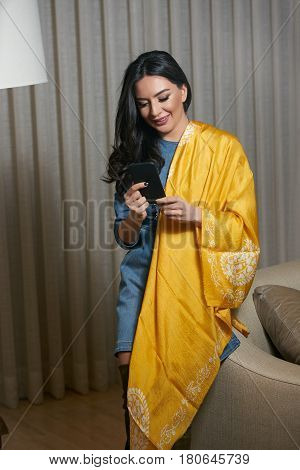 Portrait of a beautiful brunette using smartphone.young oriental beauty female  with black long hair Dressed in a denim dress clothing with Oriental yellow scarf and oriental jewelry.
