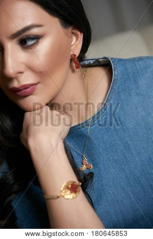 Portrait of Beautiful brunette young oriental beauty female with black long hair Dressed in a denim dress clothing with Oriental red scarf and oriental jewelry.