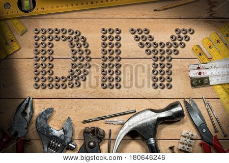 Screws in the shape of text Diy (Do it yourself) on a wooden table with work tools