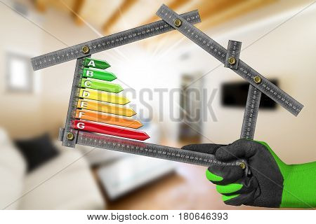Energy Efficiency - Hand with work glove holding a metal ruler in the shape of house with energy efficiency rating. Home interior