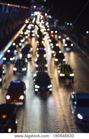 Rush hour with defocused cars and generic vehicles, traffic jam on road in night city